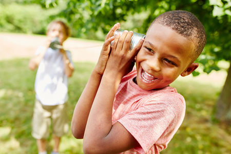 African child calling friend with tin can telephone Stockfoto