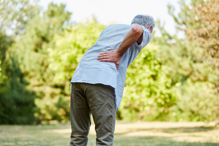 Old man with back pain while walking in the nature