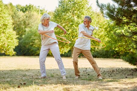 Seniors training with hula hoops in summer for his health Reklamní fotografie