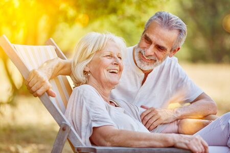 Senior couple on a summer holiday sitting on a deck chair Stock Photo