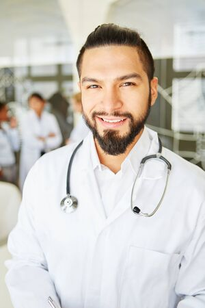 Young man as competent doctor with stethoscope at hospital