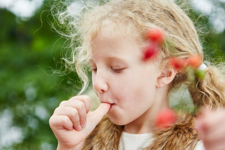 Little girl sucking her thumb and picking up rose hips in autumn Stock Photo