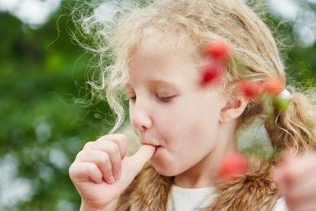 Meisje dat haar duim zuigt en rozebottels in de herfst opneemt
