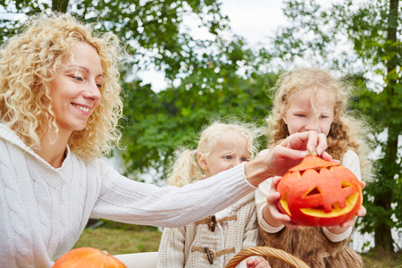 Children and woman playing with Halloween pumpkins in autumn Stock Photo