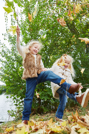 romp: Two kids playing at the park in autumn romping and moving around