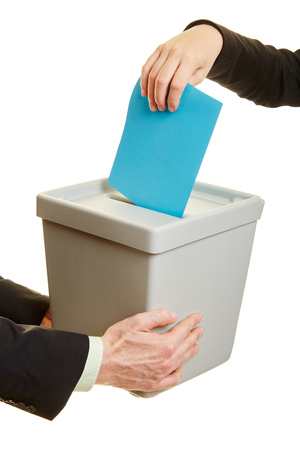Handen van mensen uit het bedrijfsleven de invoering van een stembiljet in een stembus Stockfoto - 84853909