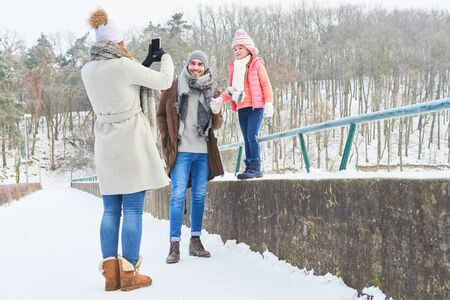 Mother takes family photograph with smartphone in winter vacation Stock Photo