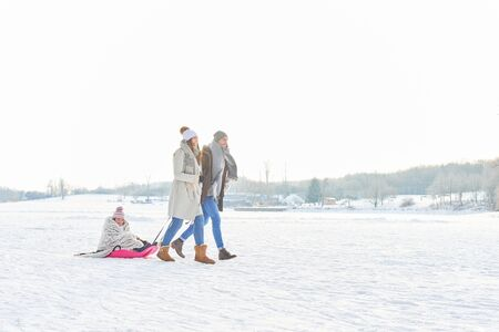 to go sledding: Family playing toboggan on the snow in winter