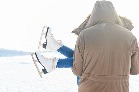 Girl wearing ice-skates has fun being carried by father in winter Stock Photo