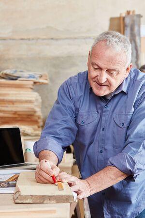 Hogere mensenhoutbewerking met nauwkeurigheid bij timmerwerkworkshop Stockfoto