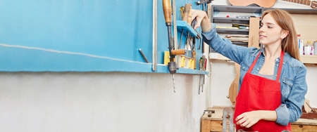 Panorama of young artisan making apprenticeship in carpenters workshop