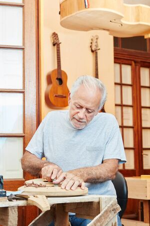 Senior guitar maker at luthiers workshop working on new guitar