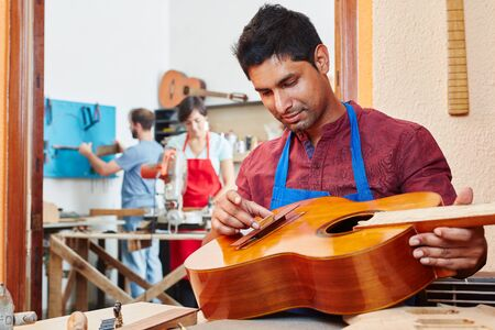 Trainee of guitar maker repairs guitar at luthiers shop Banque d'images