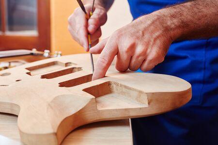 Guitar maker works on handmade guitar at carpenters workshop Banque d'images