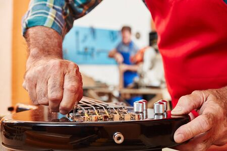 Hand of guitar maker adjusts wrench of electric guitar