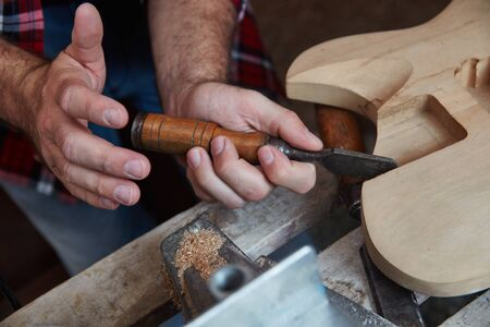 Luthier woodworking with chisel on new guitars body Banque d'images
