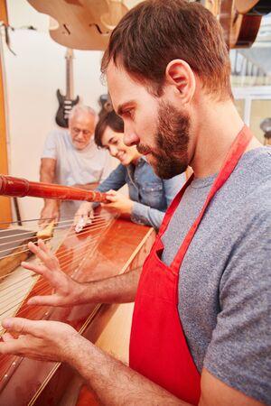 Expert luthier repairs harp carefully with his team Lizenzfreie Bilder