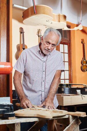Man as senior guitar maker working with wood at workshop