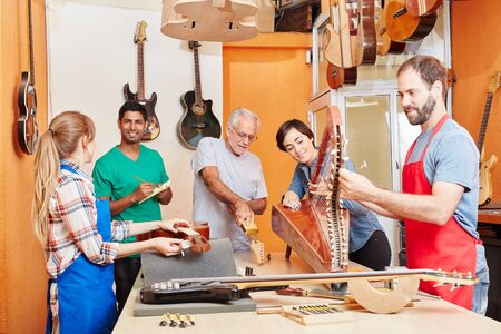 Luthier works together with team in instrument making
