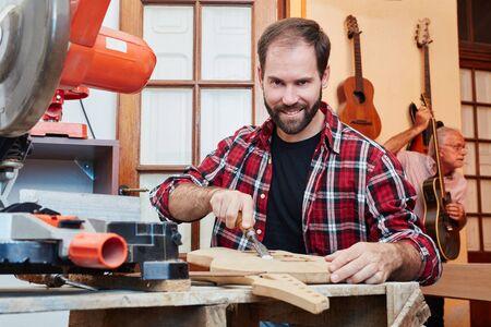 Man as craftsman making new guitar in workshop Lizenzfreie Bilder