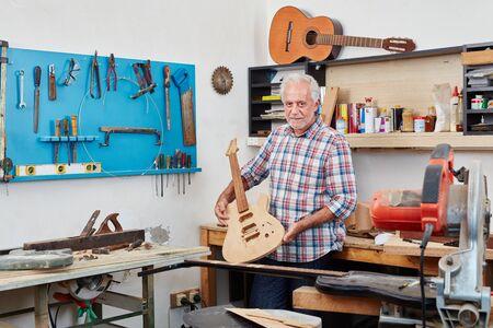 Luthier showing with pride new guitar at his workshop Lizenzfreie Bilder