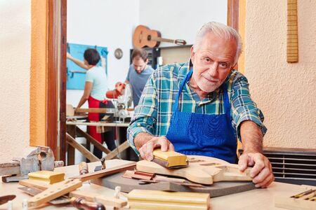 Senior luthier master prepares wood guitar with abrasive paper Banque d'images