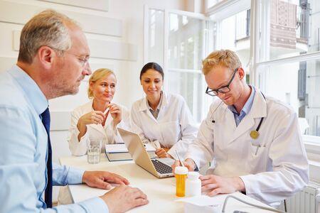Doctor writing prescription to senior patient for medicament Banque d'images