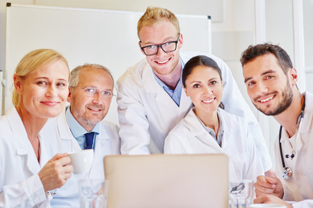 Successful team of doctors with computer in meeting Banque d'images
