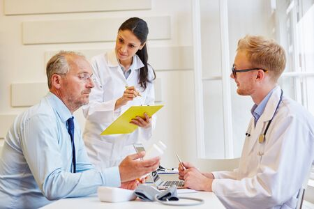 Senior citizen as patient receives therapy advice from doctors Stock Photo