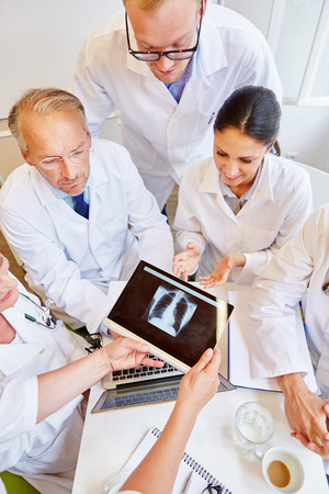 Doctors analyzing x-ray image findings on tablet computer Banque d'images