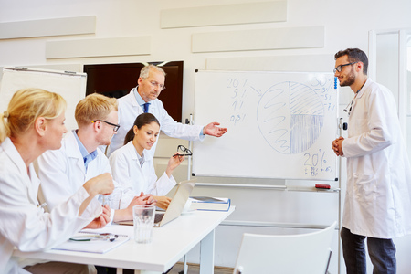 Doctors presenting during training seminar with flipchart