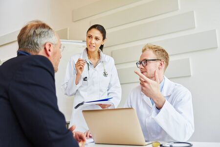 Doctors advicing patient about therapy in consultation Banque d'images