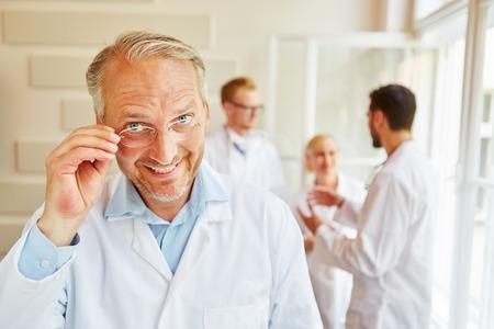 Friendly senior chief physician smiling at hospital