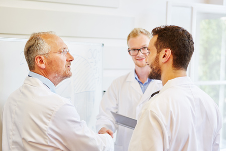 Doctors cooperating as team and shaking hands