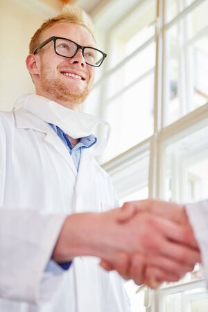Doctor sharing handshake with physician as agreement and teamwork gesture Banque d'images