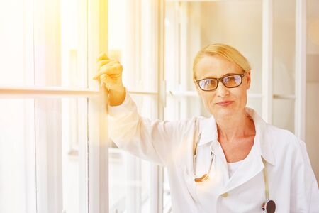 Woman with glasses as doctor leaning on window at hospital