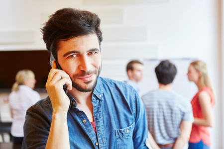 Young man as entrepreneur calling with smartphone