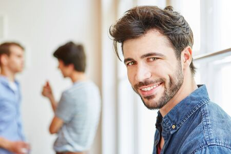 Young man as student smiling happily in his start-up company