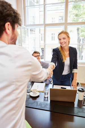 Young businesswoman welcoming man with handshake before meeting