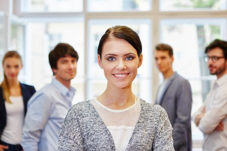 Young entreperneur woman standing and smiling in front of successful team