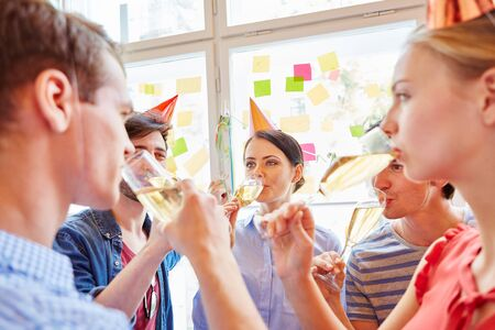 Students from start-up drinking sparkling wine in company party