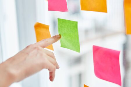 Hand pointing at sticky note with idea for business strategy Banque d'images