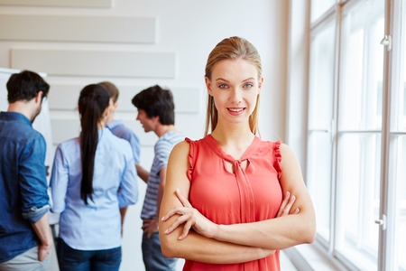 Smiling businesswoman with arms crossed in a meeting