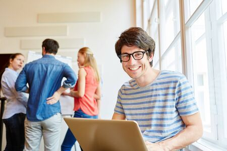 Successful student with laptop smiling with joy in a start-up