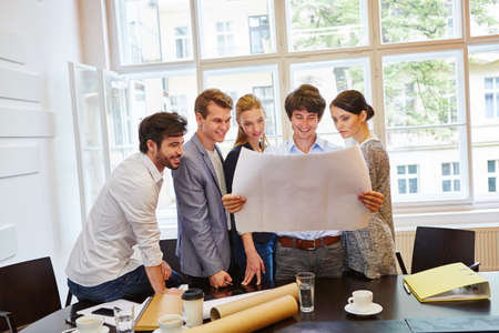 Young architechts looking at plan in start-up company