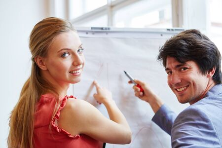 Woman and man finding solution with flipchart as a business team Banque d'images