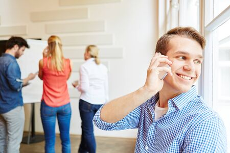 Young man calling with smartphone during start-up business meeting
