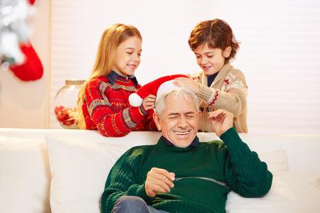 彼の頭にクリスマスとクリスマスの帽子を置くに年配の男性と遊ぶ二人の子供