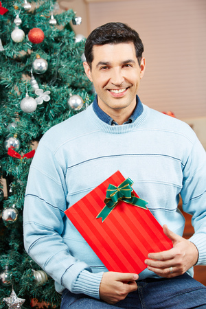 Smiling man holding a red gift at christmas tree