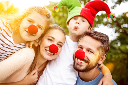 Happy family wearing clown costumes for carnival having fun Archivio Fotografico